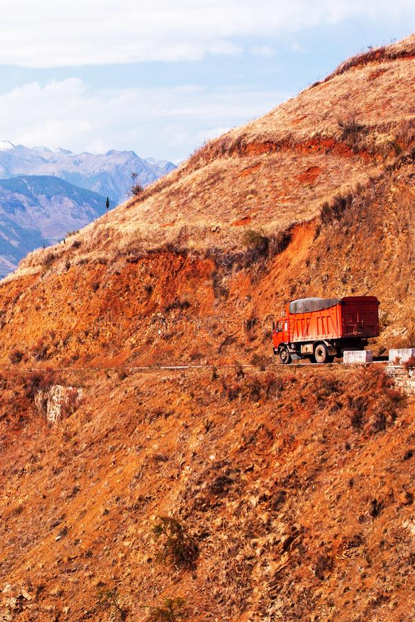 驾驶在冬天黄昏、红色山土坎意想不到的风景和雪山背景的一山路的红色卡车 免版税库存照片
