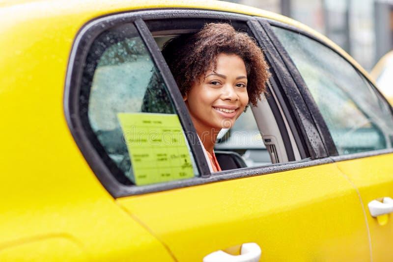 驾驶在出租汽车的愉快的非裔美国人的妇女 免版税库存图片