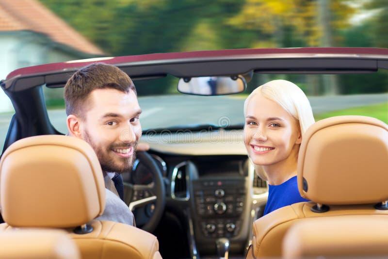 驾驶在城市的敞蓬车汽车的愉快的夫妇 免版税库存照片
