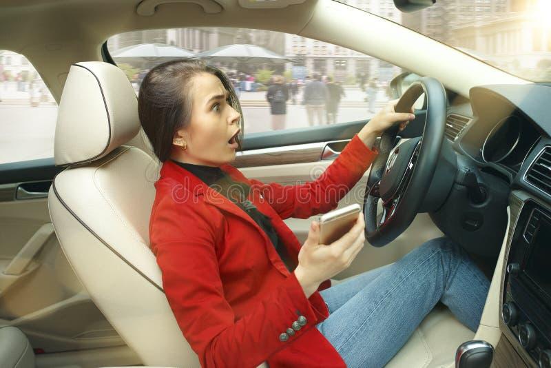 驾驶在城市附近 驾驶汽车的年轻可爱的妇女 免版税库存图片