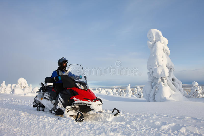 驾驶在多雪的山谷的人雪上电车 免版税库存图片