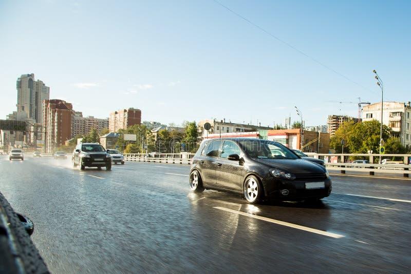 驾驶在大城市 推进调整的汽车在沥青湿路的雨中 云彩和星期日 图库摄影