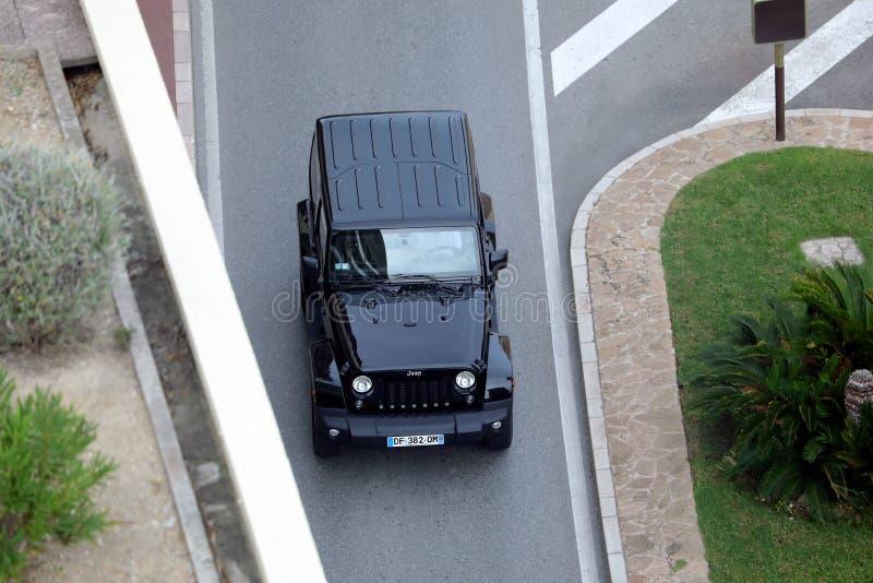 驾驶在大道Du Larvotto In摩纳哥的一个美丽的黑吉普争吵者的鸟瞰图 库存图片
