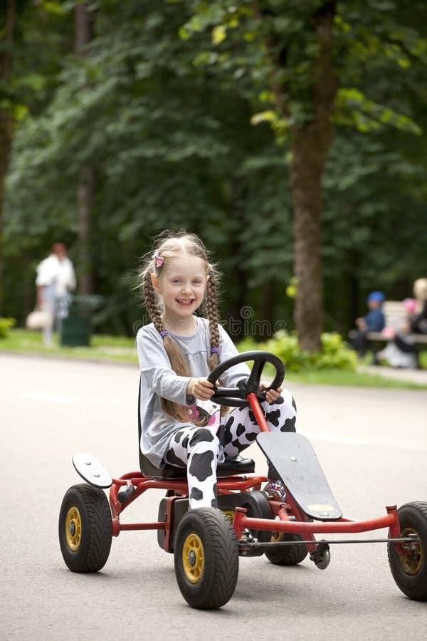 驾驶在娱乐的一个微笑的littlel女孩的画象汽车 免版税库存图片