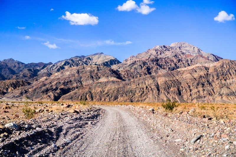 驾驶在往入口的一条未铺砌的路到泰塔斯峡谷,死亡谷国家公园;陡峭的山在背景中; 库存图片