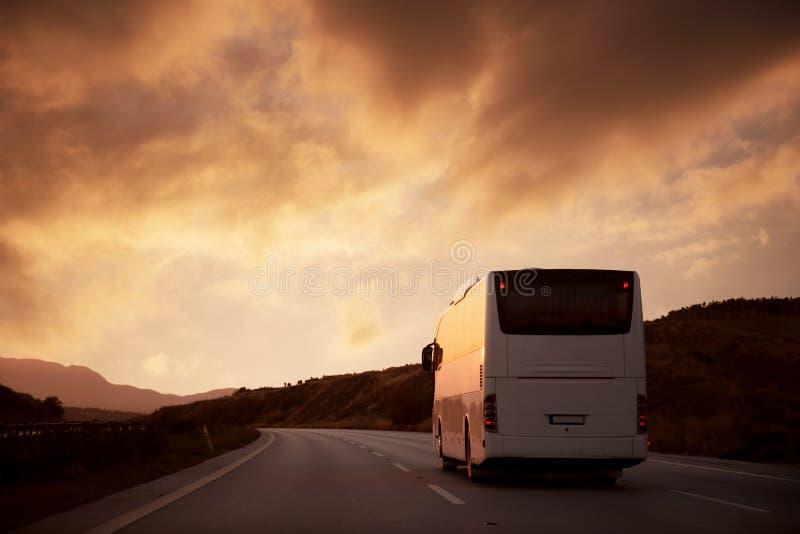 驾驶在往落日的路的白色公共汽车 库存照片