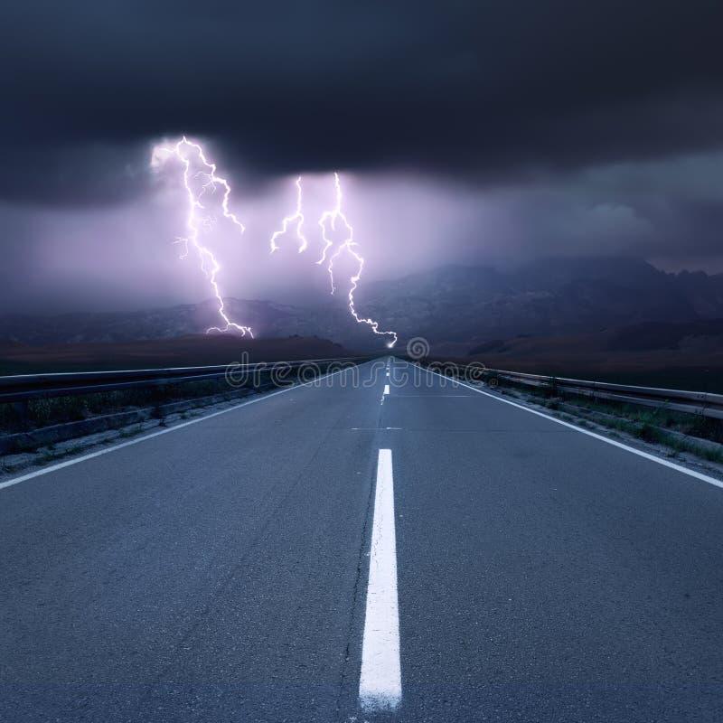 驾驶在往雷电的柏油路 库存图片