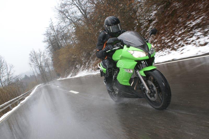 驾驶在恶劣天气的一辆摩托车 库存图片