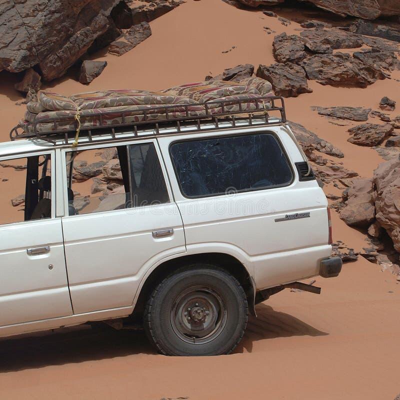 驾驶在撒哈拉大沙漠的游人吉普 库存照片