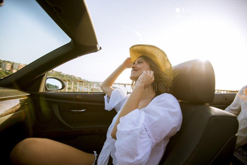 驾驶在敞蓬车的年轻可爱的妇女在海边 免版税图库摄影
