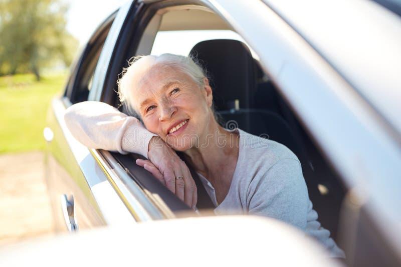 驾驶在有开窗口的汽车的愉快的资深妇女 免版税库存图片