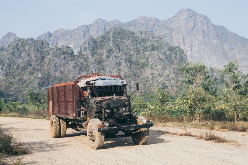 驾驶在有Zwegabin山的土路的老卡车在背景在Hpa-An,缅甸 免版税图库摄影