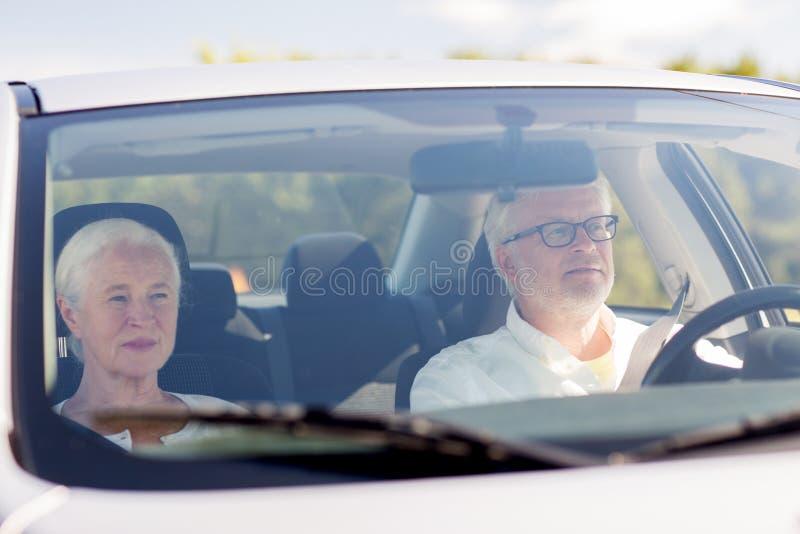 驾驶在汽车的愉快的资深夫妇 免版税库存图片