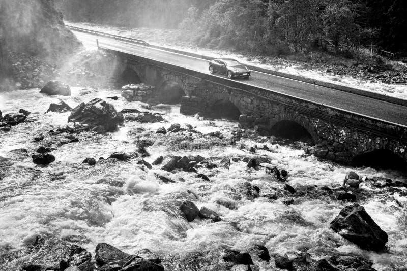 驾驶在老石桥梁横穿河急流的跑车 免版税库存照片