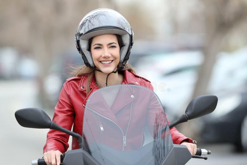 驾驶在街道上的妇女一辆滑行车 库存照片