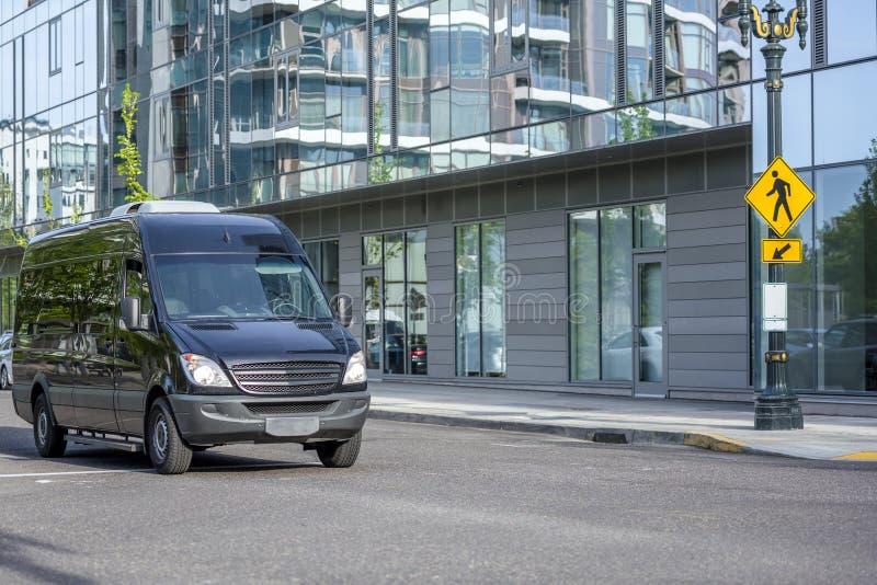 驾驶在都市城市街道上的黑紧凑商业微型搬运车 免版税库存图片