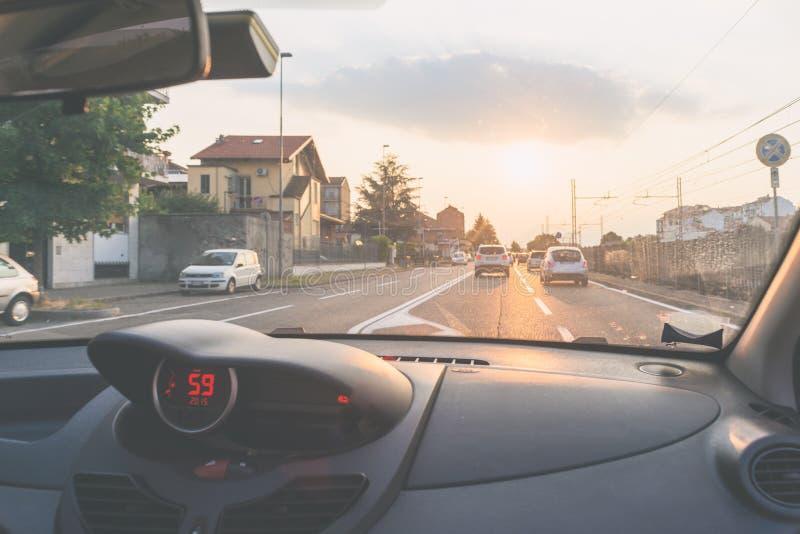驾驶在都市街道的汽车有从里边交通的,看法,挡风玻璃车内部,背后照明,定了调子葡萄酒 免版税库存图片