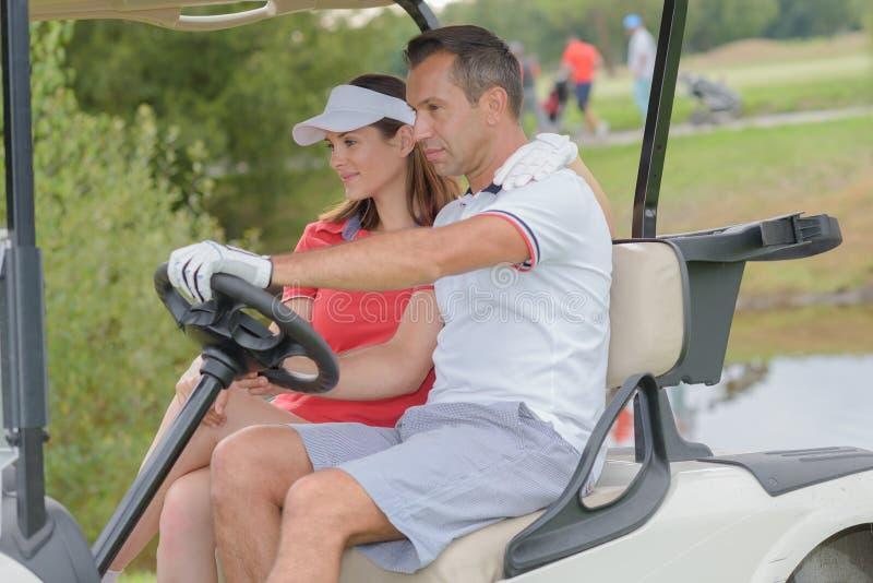 驾驶在高尔夫球场的夫妇高尔夫球儿童车 库存图片