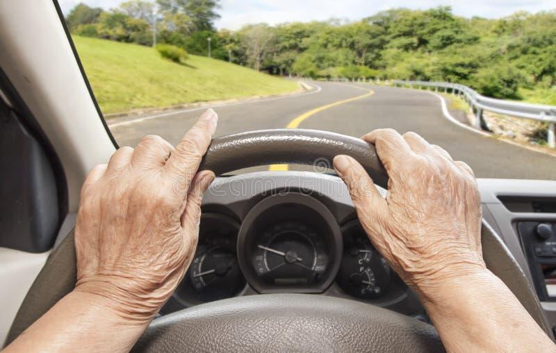 驾驶在高速公路的资深妇女一辆汽车 免版税图库摄影