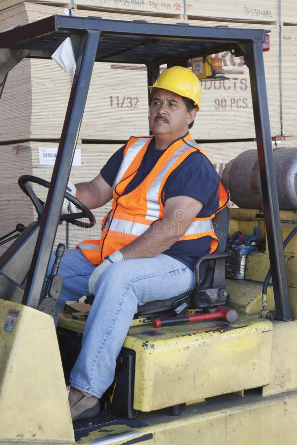 驾驶在仓库里的铲车司机 免版税库存图片