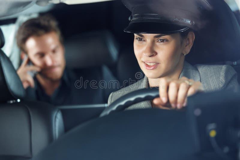驾驶大型高级轿车的女性汽车夫 免版税图库摄影