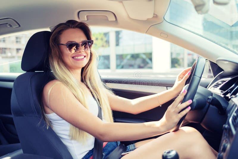 驾驶她新的现代汽车的愉快的时兴的年轻女人 库存图片