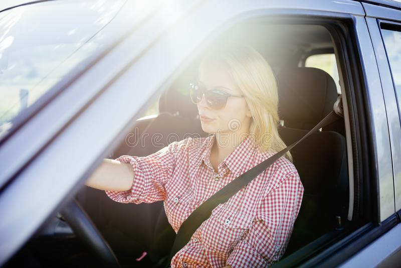 驾驶她新的豪华汽车的愉快的年轻女人司机 免版税库存图片