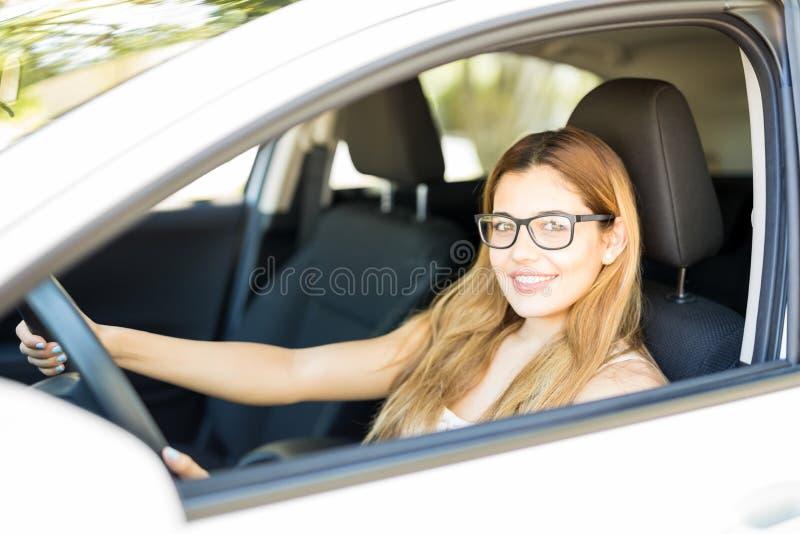 驾驶她的汽车的可爱的妇女 库存图片