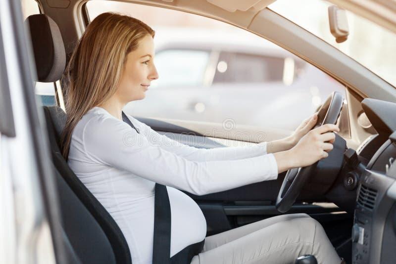 驾驶她的汽车的孕妇 免版税库存照片
