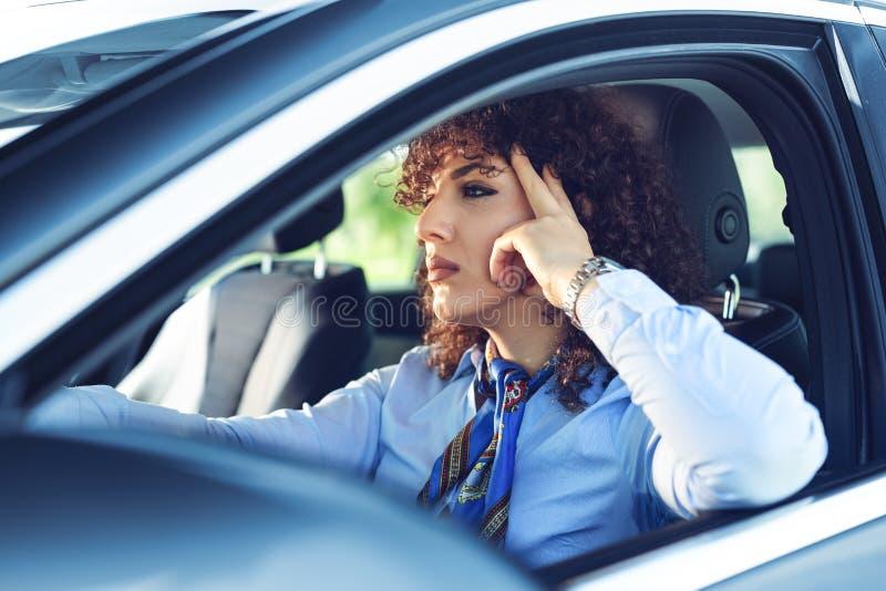 驾驶她的汽车的美丽的愉快的妇女 免版税库存图片