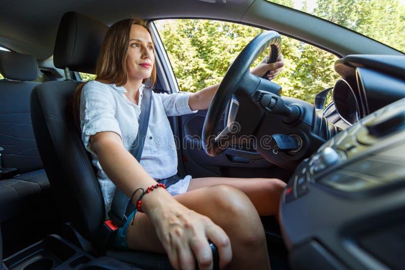 驾驶她自己或租汽车的年轻女人 免版税库存照片