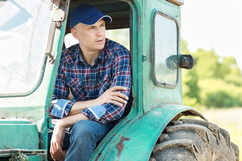 驾驶拖拉机的农夫在乡下 免版税库存照片