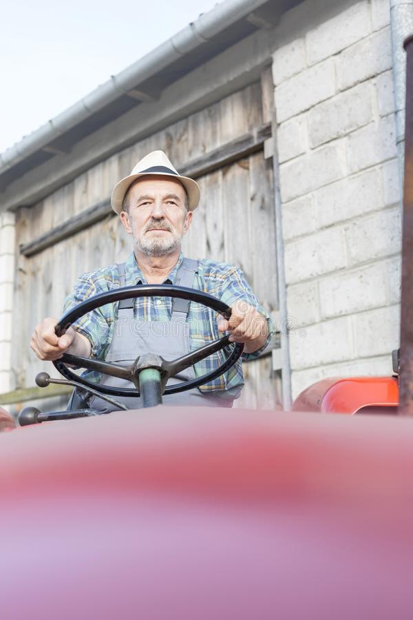 驾驶拖拉机的资深农夫反对谷仓在农场 库存照片