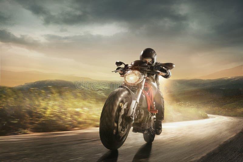 驾驶摩托车的黑盔甲的摩托车骑士 免版税图库摄影