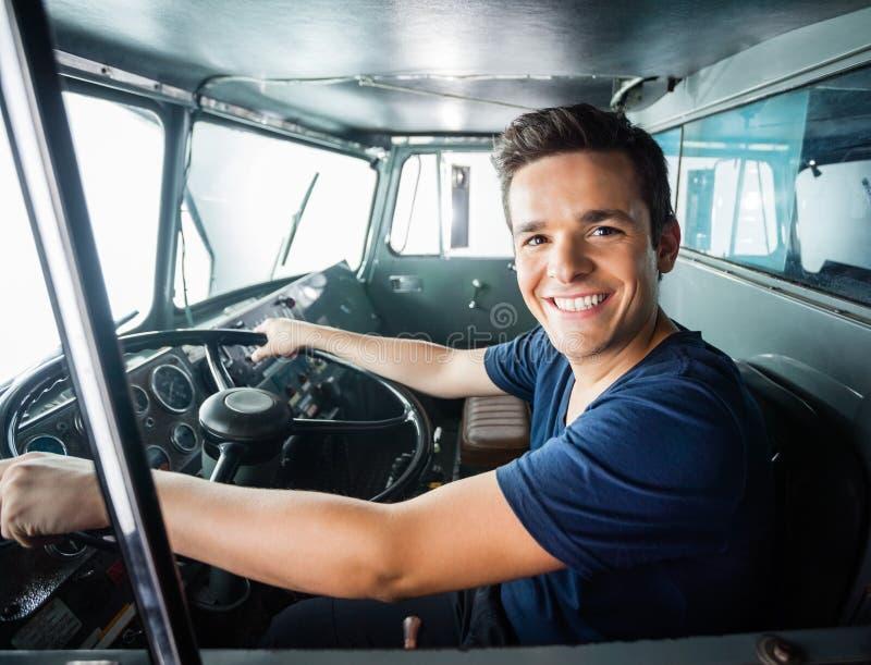 驾驶救火车的愉快的消防员 免版税库存照片