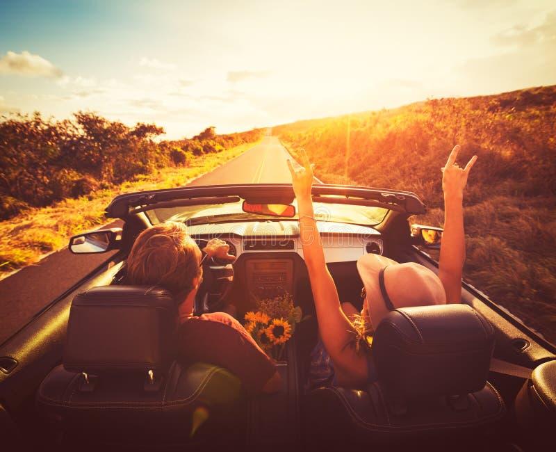 驾驶敞篷车的夫妇在日落 免版税库存图片