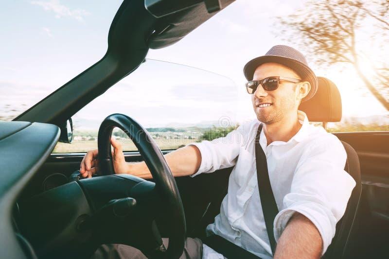 驾驶敞蓬车汽车的微笑的人由在汽车视图里面的省山路 库存图片