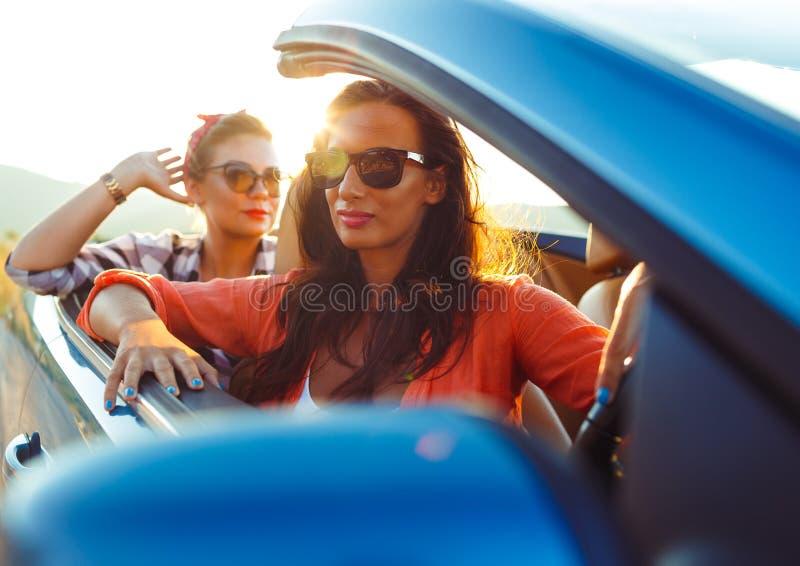 驾驶敞蓬车的两个女孩 免版税库存照片