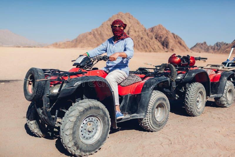 驾驶方形字体自行车的老人在西奈沙漠 愉快的游人获得乐趣在暑假时 免版税库存图片