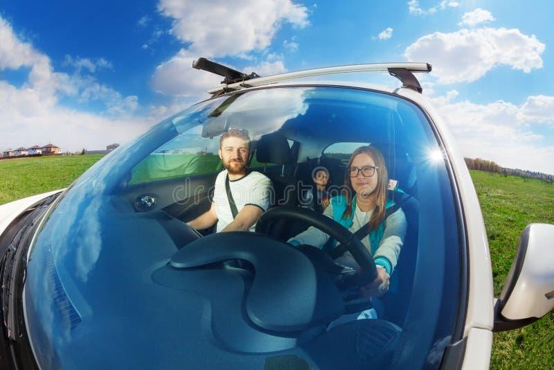 驾驶有她的家庭的年轻母亲汽车 免版税库存照片