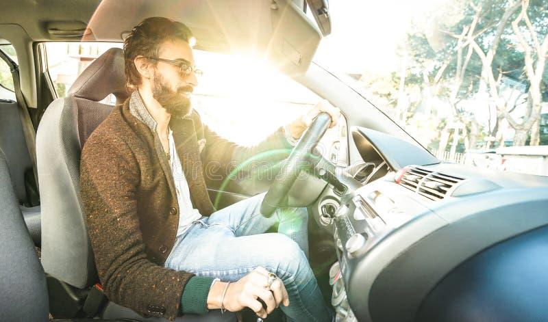 驾驶有胡子和供选择的髭的年轻行家时装模特儿车的愉快的确信的人微笑对企业roadtrip - 免版税图库摄影