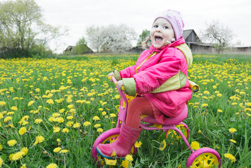 驾驶横跨春天开花的蒲公英草甸的呼喊的小女孩桃红色和黄色周期 免版税库存照片