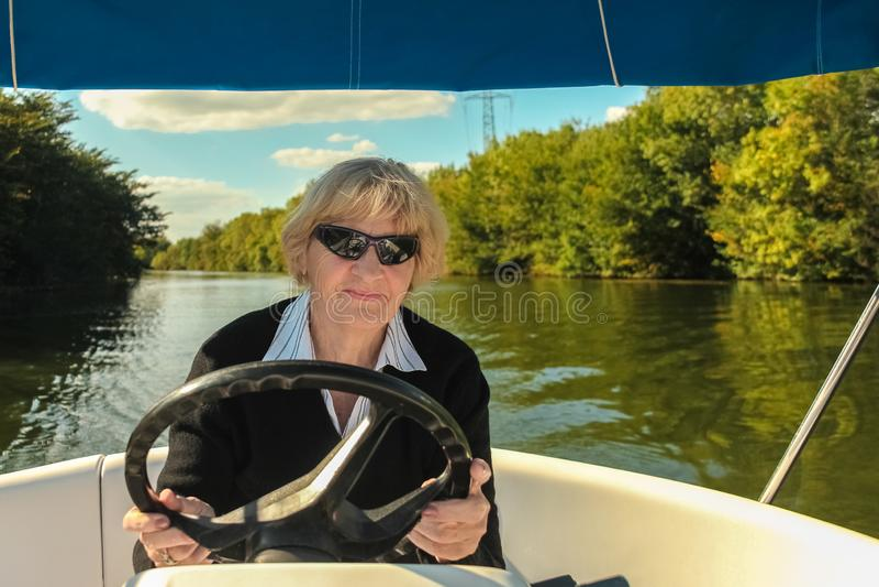 驾驶汽艇的愉快的微笑的资深妇女在河,假期旅行概念 免版税库存图片