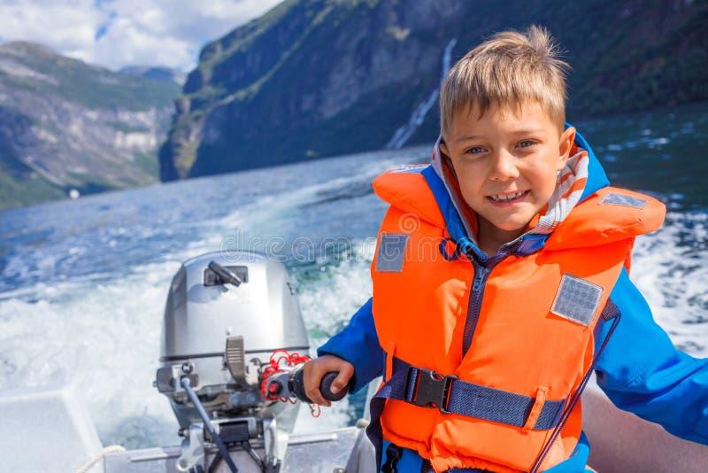 驾驶汽艇,挪威的男孩关闭画象 他享受片刻 免版税库存照片