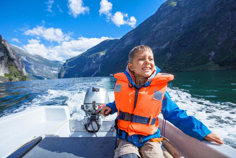 驾驶汽艇,挪威的男孩关闭画象 他享受片刻 库存图片