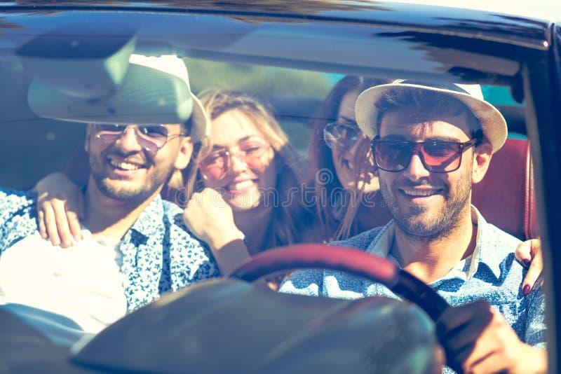 驾驶汽车和微笑在夏天的小组快乐的年轻朋友 免版税库存图片