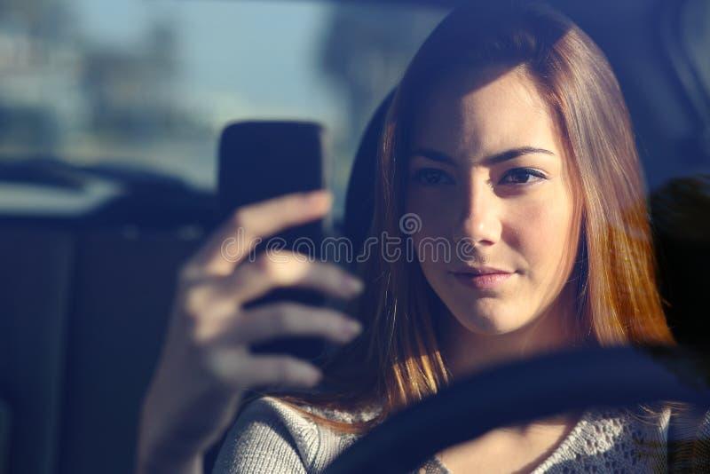 驾驶汽车和键入在一个巧妙的电话的妇女的正面图 免版税库存图片