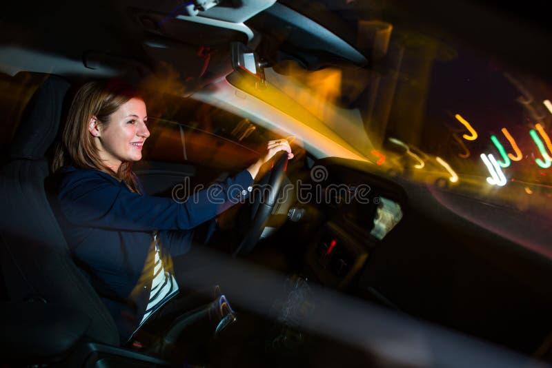 驾驶汽车在晚上-相当,驾驶她的汽车的少妇 免版税图库摄影