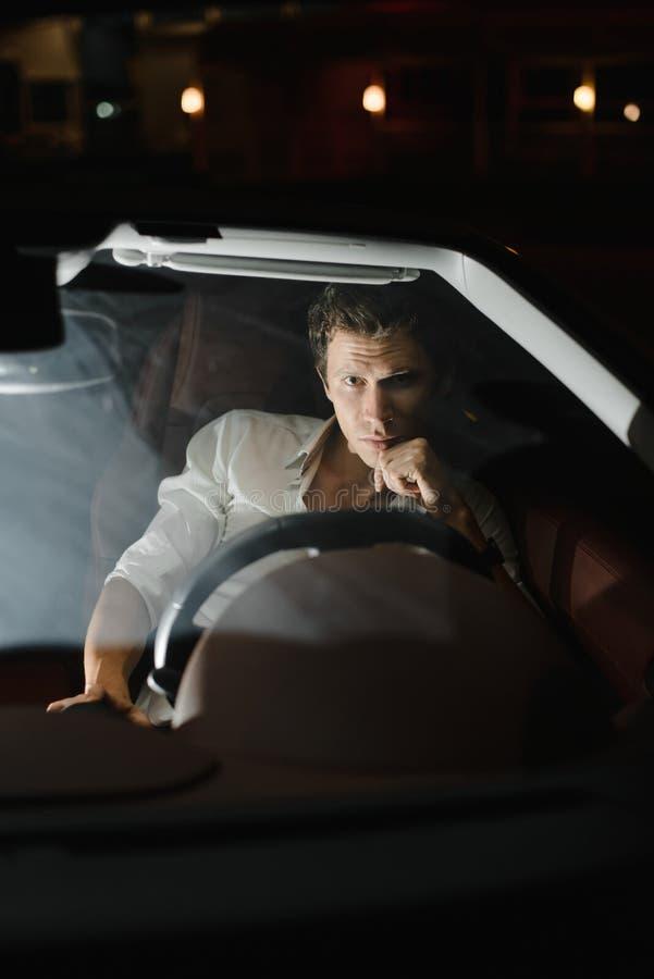 驾驶汽车敞蓬车的英俊的时尚人 豪华 生活晚上 在他后的红灯 库存照片
