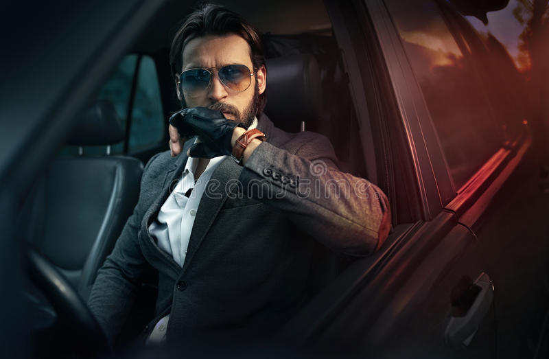 驾驶汽车的典雅的英俊的人 免版税库存照片